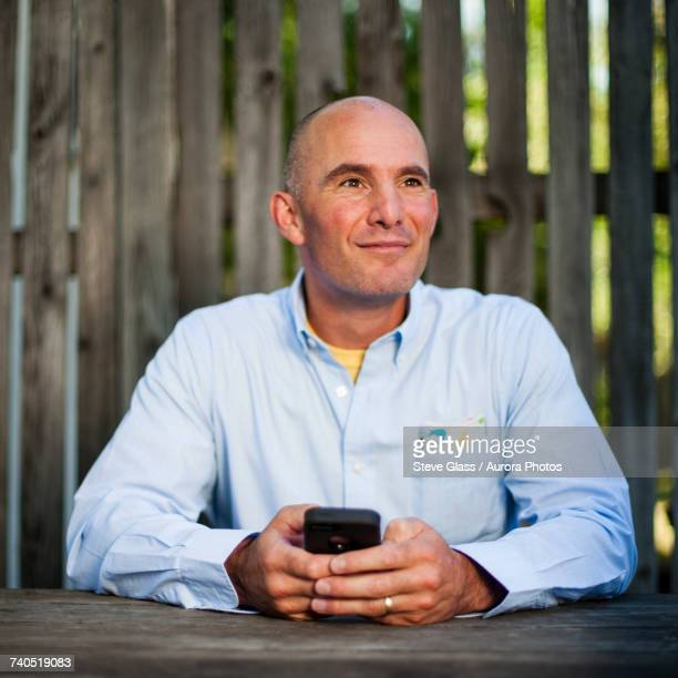 Man sitting with cell phone at wooden table, fence in background
