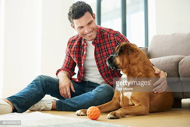 Man sitting with dog on living room floor playing