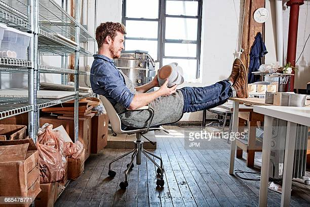 Man sitting with feet up in pottery workshop