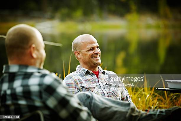 Man sitting with friends by lake smiling