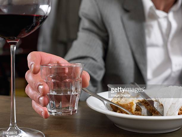 Man sitting with glass of water and finished meal