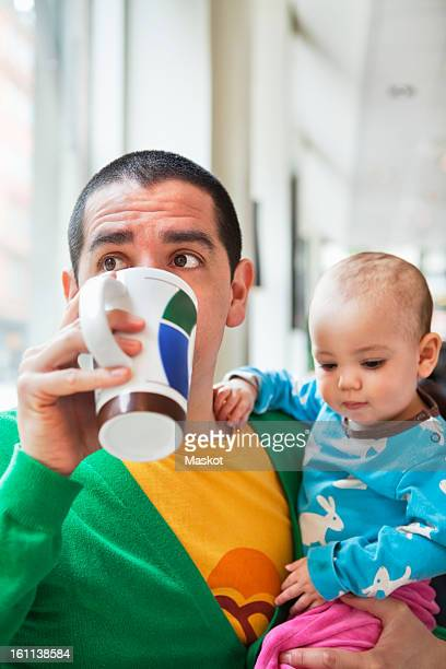 man sitting with his daughter (0-11 months) drinking coffee - 0 11 monate stock-fotos und bilder