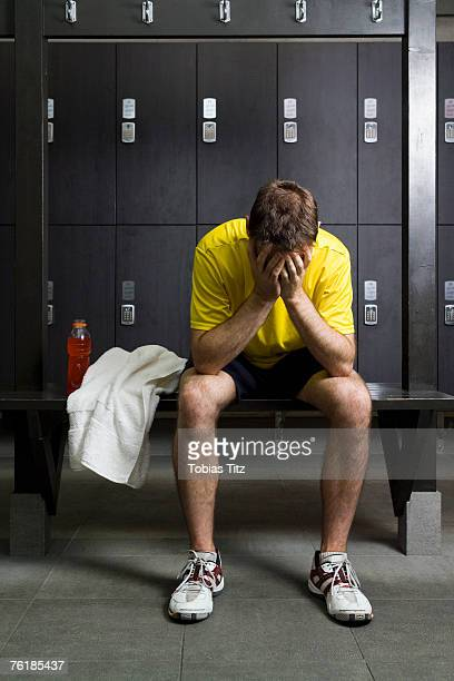 A man sitting with his head in his hands in a locker room
