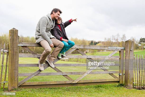 man sitting with his son on the gate of a cottage - belgium stock pictures, royalty-free photos & images