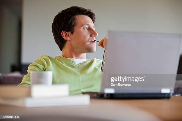 mann, sitzend mit laptop und denken - abgelenkt stock-fotos und bilder