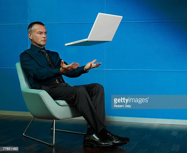man sitting with laptop floating over his lap - illusion stock pictures, royalty-free photos & images