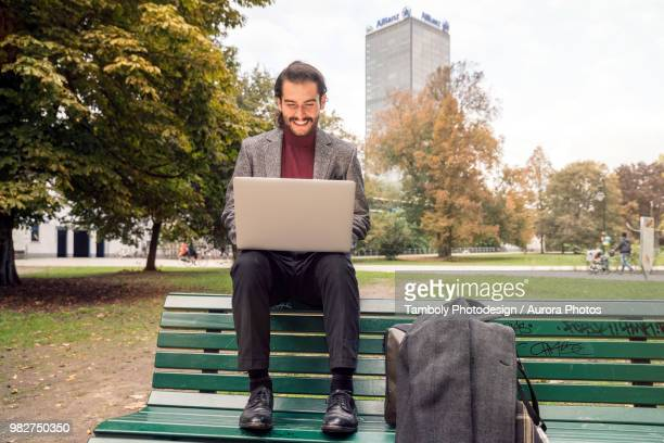 man sitting with laptop on bench in park - よそいきの服 ストックフォトと画像