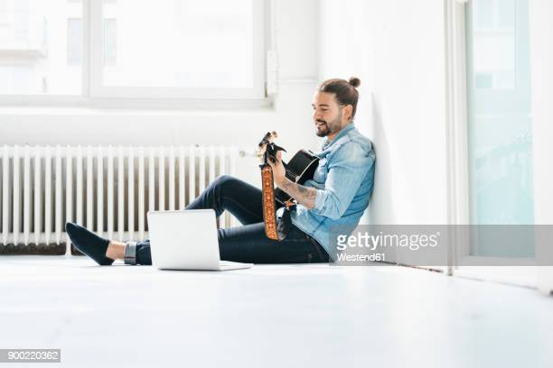 man sitting with laptop on floor playing guitar - komponist stock-fotos und bilder