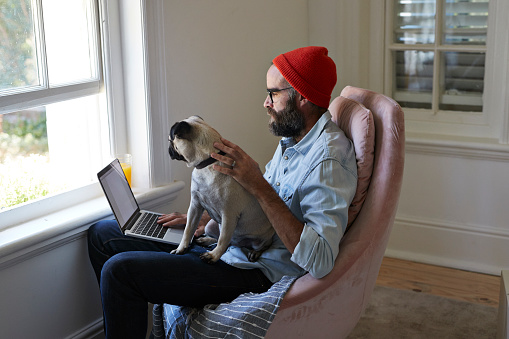 Man sitting with laptop together with Puck dog - gettyimageskorea