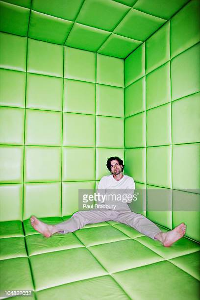 Man sitting with legs apart in padded room