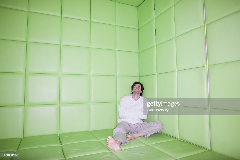 Man sitting with legs apart in padded room : Stock Photo