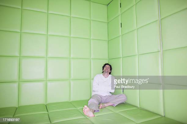 man sitting with legs apart in padded room - straight jacket stock pictures, royalty-free photos & images