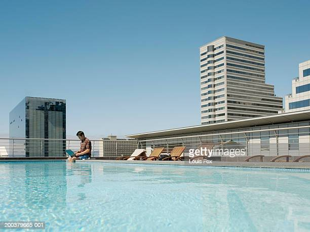 Man sitting with legs in swimming pool, laptop on lap