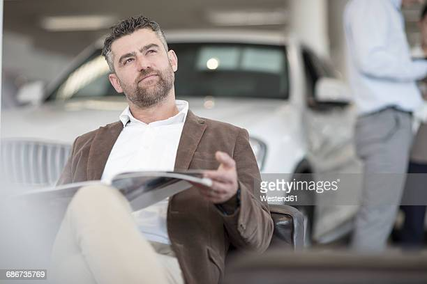Man sitting with magazine at car dealership