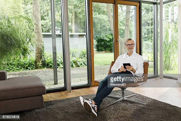 Man sitting with tablet on chair in his living room