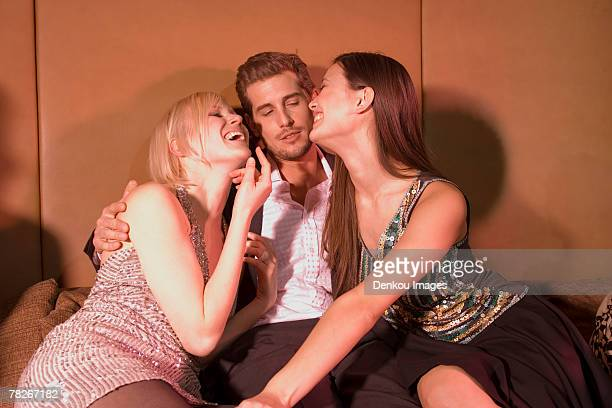 man sitting with two women at a nightclub. - gigolo stock photos and pictures