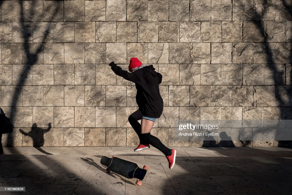 Man Skateboarding Against Wall : Stock Photo
