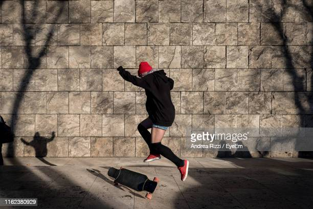 man skateboarding against wall - andrea rizzi stock pictures, royalty-free photos & images
