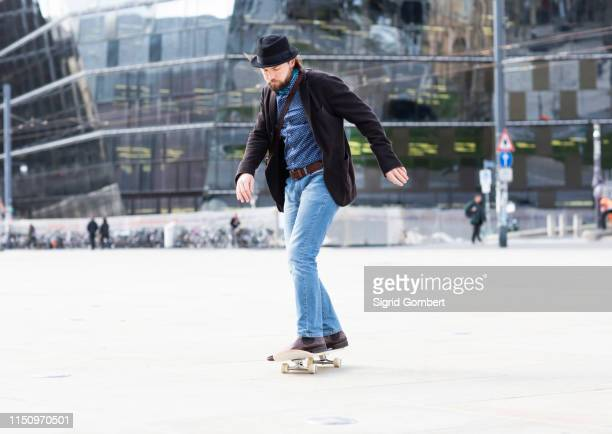 man skateboarding in city square, freiburg, baden-wurttemberg, germany - sigrid gombert stockfoto's en -beelden
