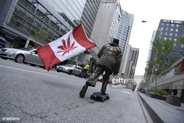 A man skateboarding in downtown waiving a replica of a Canadian flag where the maple leaf has been replaced by Marijuana leaves during the Global...