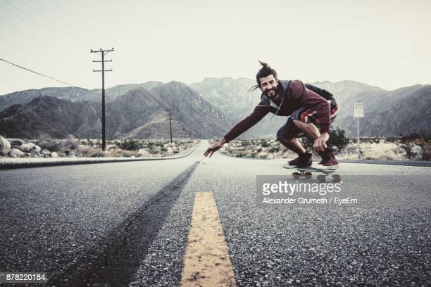 man skateboarding on road against clear sky - baden württemberg stock photos and pictures