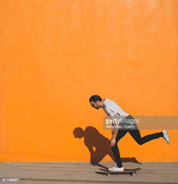 man skateboarding on street against yellow wall - unterwegs stock-fotos und bilder