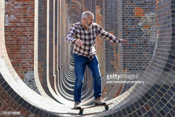 man skateboarding underneath viaduct - viaduct stock pictures, royalty-free photos & images