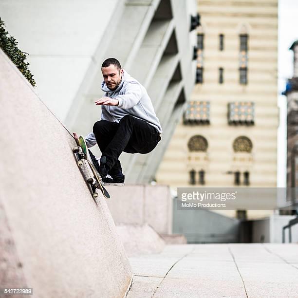 Man skateboarding up half wall.