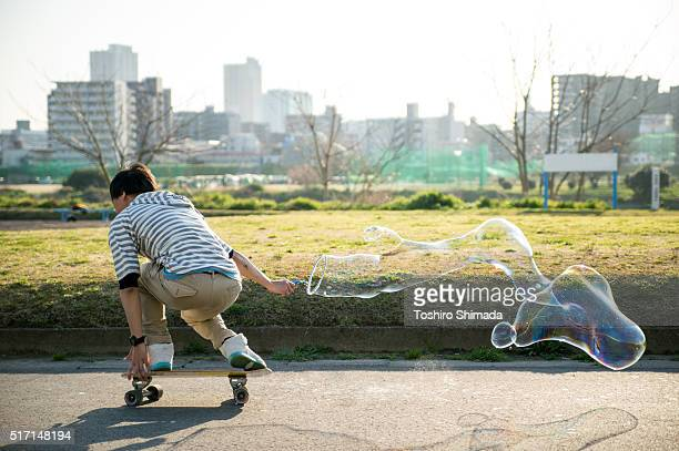 A man skateboarding with bubble soaping
