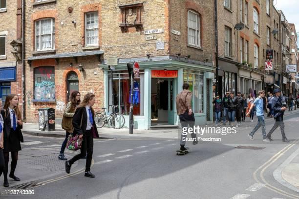 Man skateboards down Brick Lane as people cross the road. London, United Kingdom.
