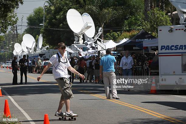 A man skateboards past television news trucks that line the street in front of the Jackson family mansion to report on the death of singer Michael...
