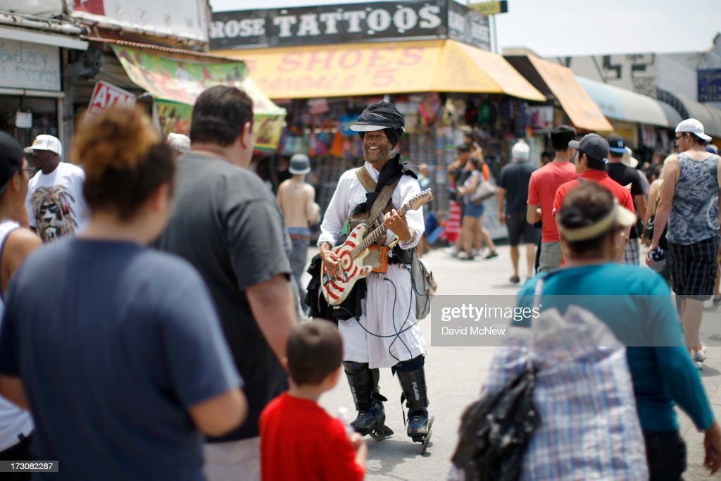 A man skates and plays electric guitar to solicit tips from passersby on Independence Day weekend at Venice Beach on July 6, 2013 in Venice, California. An estimated 16 million people visit the famous beach city annually which is celebrating 108th birthday as of July 4.