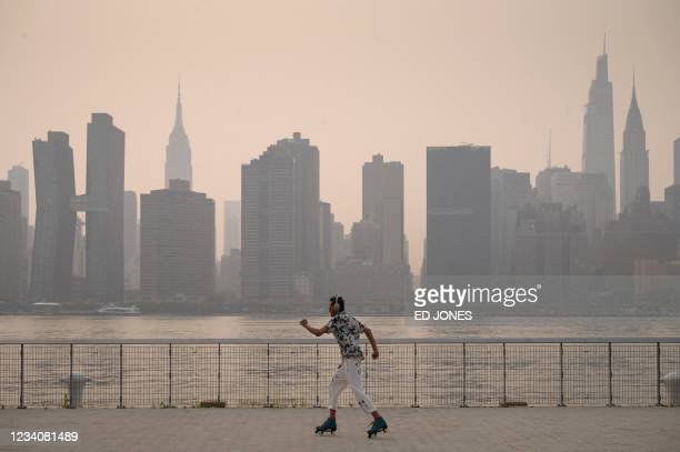 Man skates before the Manhattan city skyline at a park in the Brooklyn borough of New York on July 20, 2021. - Domestic media reported that smoke...
