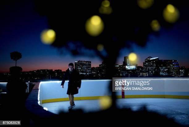 A man skates on synthetic ice atop the Watergate Hotel November 16 2017 in Washington DC / AFP PHOTO / Brendan Smialowski