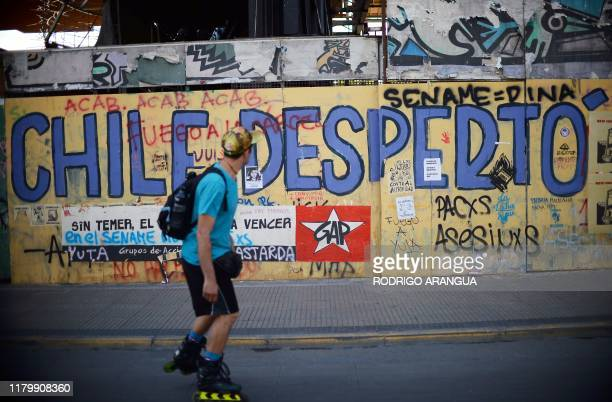 A man skates passing by a graffiti that reads Chile woke up in Santiago on November 03 2019 Protesters angry about the cost of living and a yawning...