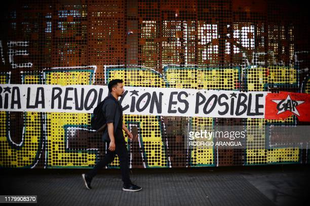 TOPSHOT A man skates passing by a graffiti that reads Revolution is possible in Santiago on November 03 2019 Protesters angry about the cost of...