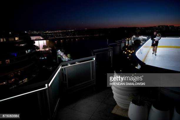 TOPSHOT A man skates with his child on synthetic ice atop the Watergate Hotel November 16 2017 in Washington DC / AFP PHOTO / Brendan Smialowski