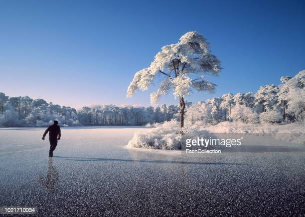Man skating on frozen lake on a beautiful sunny morning
