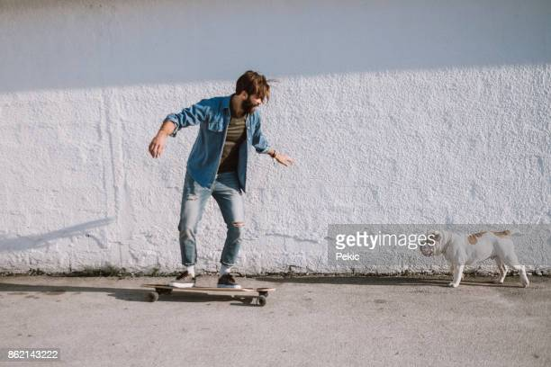 mann mit hund - longboard skating stock-fotos und bilder