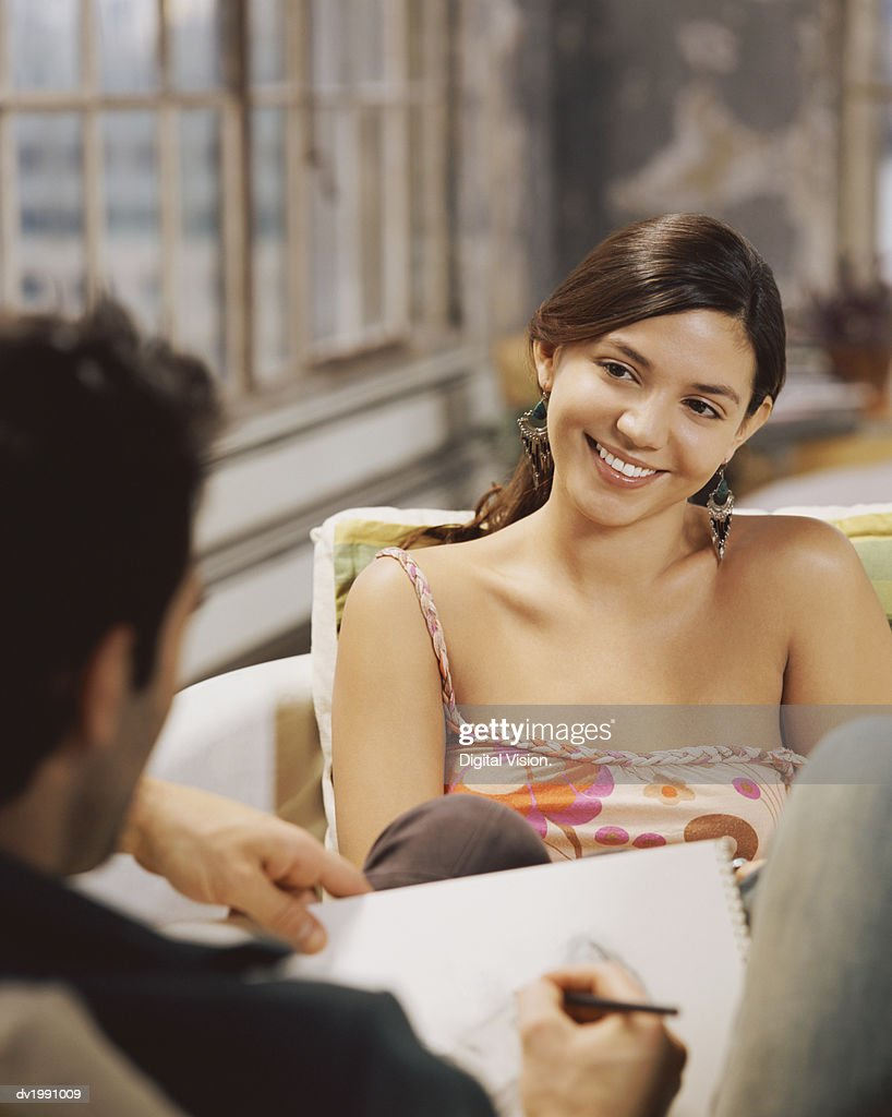 Man Sketching a Woman in an Apartment : Stock Photo
