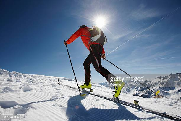 man ski touring up a mountain - langlaufen stockfoto's en -beelden