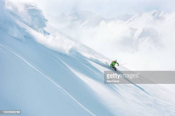 man skiing down a steep slope on fresh snow - european alps stock pictures, royalty-free photos & images