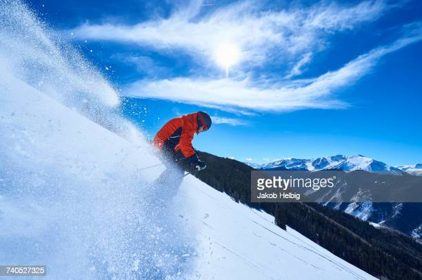 Man skiing down deep snow covered mountainside, Aspen, Colorado, USA