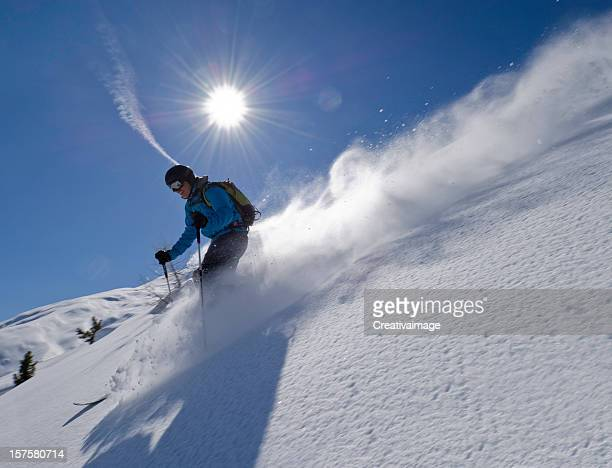 Man skiing down slope with blue sky and sun background