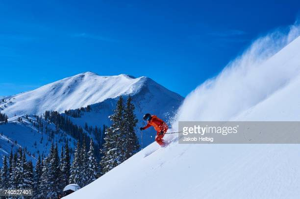 man skiing down steep snow covered mountainside, aspen, colorado, usa - aspen colorado stock photos and pictures