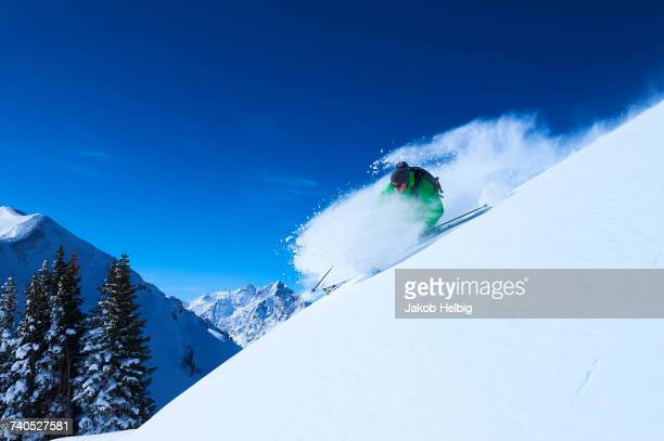 Man skiing down steep snow covered mountainside, Aspen, Colorado, USA