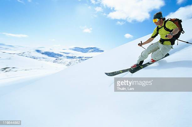 man skiing in mountain scenery - downhill skiing stock pictures, royalty-free photos & images