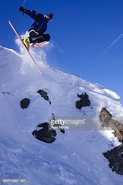 man skiing, jumping off mountain ledge, low angle view - female skier stock pictures, royalty-free photos & images