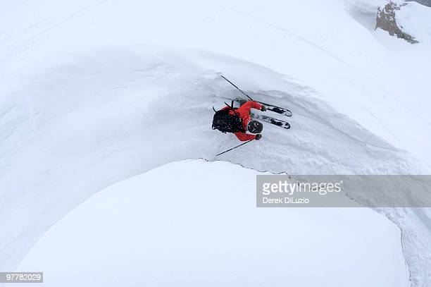 a man skiing next to a rock in jackson hole, wyoming. - jackson hole stock pictures, royalty-free photos & images