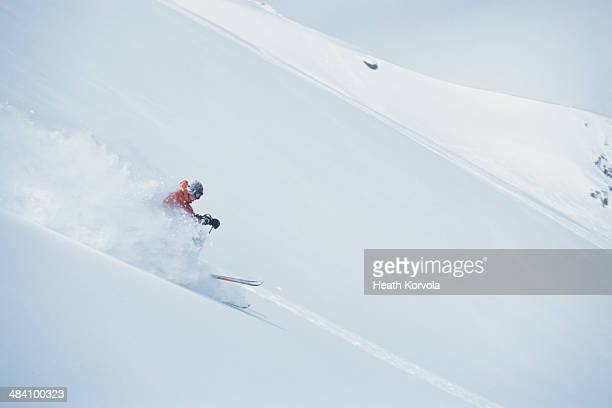 Man skiing on ideal slope in deep powder.